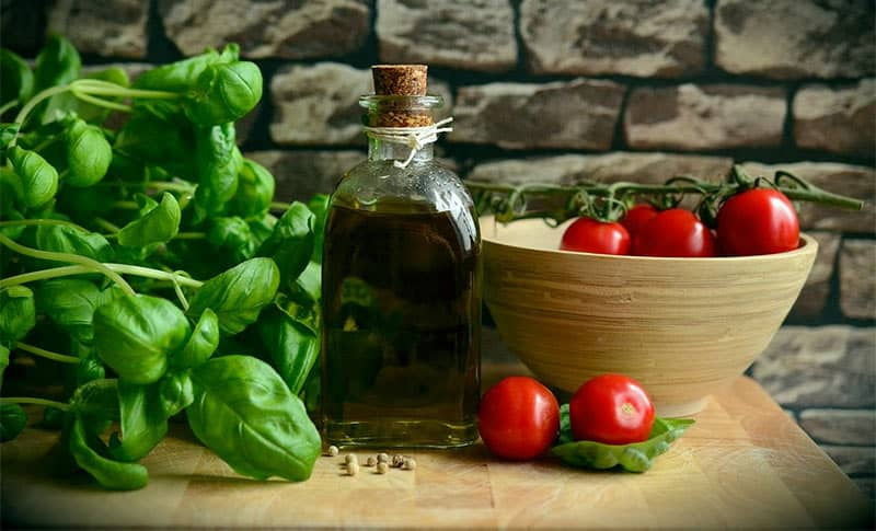 fresh basil with tomatoes and olive oil on counter